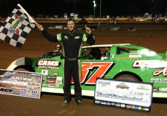 Walker Arthur of Forest, VA raises the checkered flag in victory after winning the 50-lap NeSmith Chevrolet Dirt Late Model Series main event on Saturday night driving the Cecil B. Arthur Beef Farms Special in the Super Bowl of Racing Presented By Rock Auto.com at Golden Isles Speedway in Brunswick, GA  (NeSmith Racing Photo)
